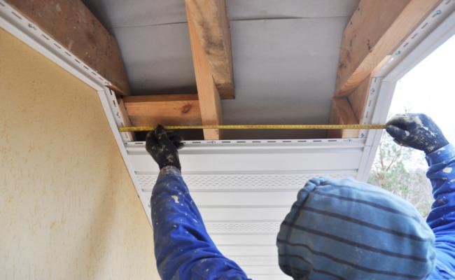 A man installing Soffits